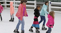 In pairs and on their own, skaters slide around the Library Lawn Skate Rink, next to the Lawrence Public Library, 707 Vermont St., on Saturday, Dec. 26. The rink features a simulated-ice surface and rents skates.