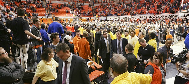 Oklahoma State security helps to shield as Kansas head coach Bill Self and his staff leave the court following the Jayhawks' 86-67 loss to Oklahoma State on Tuesday, Jan. 19, 2016 at Gallagher-Iba Arena in Stillwater, Okla.
