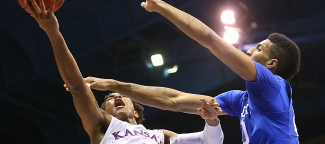 Kansas guard Devonte' Graham (4) puts a shot off the glass as he is fouled by Kentucky forward Marcus Lee (00) during the second half, Saturday, Jan. 30, 2016 at Allen Fieldhouse.