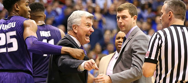 Kansas State head coach Bruce Weber is pulled back by Kansas State forward Wesley Iwundu (25) while disputing an out-of-bounds ball during the first half on Wednesday, Feb. 3, 2016 at Allen Fieldhouse.
