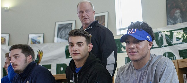 Free State High senior Bryce Torneden, right, is introduced by FSHS football coach Bob Lisher, standing, before Torneden signed a letter of intent to play at Kansas University next year. Also signing letters of intent with colleges Wednesday at FSHS, from left, are Firebirds Garrett Swisher, left, with Highland Community College, and Drew Tochtrop, with Hutchinson Community College.