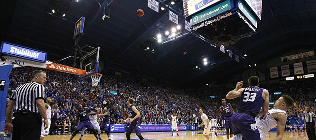 Kansas guard Brannen Greene watches his three from the corner go in as he is fouled by Kansas State guard Brian Rohleder (33) with second remaining in the first half on Wednesday, Feb. 3, 2016 at Allen Fieldhouse. Greene hit the free throw to complete the four-point play.