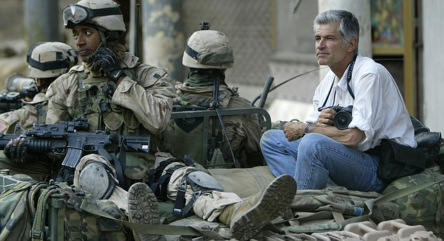 U.S. award-winning photojournalist James Nachtwey, right, rides on the top of a U.S. Humvee during a patrol in central Baghdad in this April 17, 2003 photo.