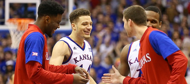 Kansas guard Brannen Greene, second from left, is congratulated by teammates after a three during the second half, Tuesday, Jan. 9, 2016 at Allen Fieldhouse.