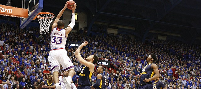 Kansas forward Landen Lucas (33) gets up for a lob dunk against West Virginia forward Nathan Adrian (11) during the first half, Tuesday, Jan. 9, 2016 at Allen Fieldhouse.