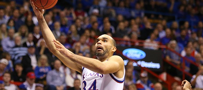 Kansas forward Perry Ellis (34) gets in for a bucket past West Virginia forward Elijah Macon (45) and forward Esa Ahmad (23) during the first half, Tuesday, Jan. 9, 2016 at Allen Fieldhouse.