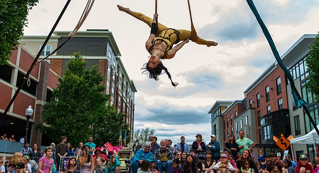 Mariel Reynolds, of Kansas City, Mo., hangs upside down, suspended above New Hampshire St. in front of the Lawrence Arts Center, as she performs with the aerial performance group Voler - Thieves of Flight while spectators watch as part of the annual Lawrence Busker Festival, Sunday, May 31, 2015.