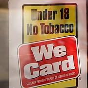 Signs warning against the sale of tobacco to minors are displayed in the window of a Lawrence store, Thursday, Feb. 11, 2016.