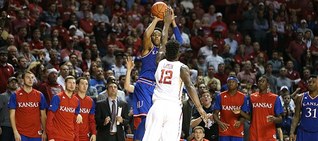Kansas guard Devonte' Graham (4) drills a huge three over Oklahoma forward Khadeem Lattin (12) late in the second half, Saturday, Feb. 13, 2016 at Lloyd Noble Center in Norman, Okla.