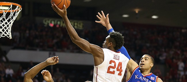 Kansas forward Landen Lucas (33) and guard Wayne Selden Jr. (1) defend against a drive by Oklahoma guard Buddy Hield (24) during the first half, Saturday, Feb. 13, 2016 at Lloyd Noble Center in Norman, Okla.