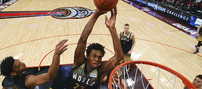 World forward Andrew Wiggins dunks past United States' Jahlil Okafor, left, during the second half of the NBA Rising Stars Challenge basketball game in Toronto on Friday, Feb. 12, 2016. (Elsa/Pool Photo via AP)