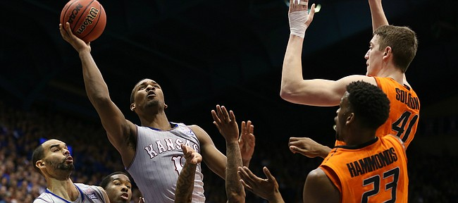 Kansas guard Wayne Selden Jr. (1) puts up a shot against  Oklahoma State guard Tyree Griffin (2), guard Leyton Hammonds and forward Mitchell Solomon during the second half, Monday, Feb. 15, 2016 at Allen Fieldhouse. At left are Kansas forward Perry Ellis (34) and Oklahoma State guard Tavarius Shine (5).
