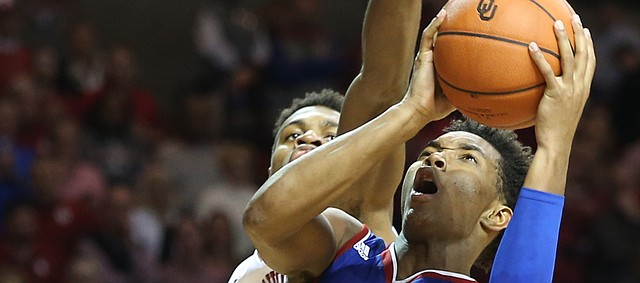 Kansas guard Devonte' Graham (4) gets under Oklahoma guard Buddy Hield (24) for a shot during the second half, Saturday, Feb. 13, 2016 at Lloyd Noble Center in Norman, Okla.