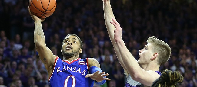 Kansas guard Frank Mason III (0) puts up a shot against Kansas State forward Dean Wade (32) during the first half, Saturday, Feb. 20, 2016 at Bramlage Coliseum in Manhattan, Kan. In front is Kansas State forward D.J. Johnson (4).