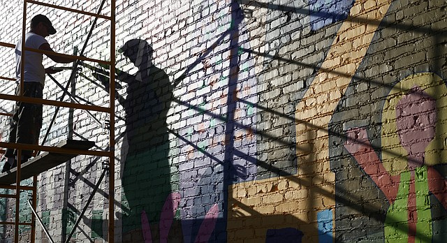 "Lawrence artist Dave Loewenstein works on a mural in Joplin, Mo., in this image from ""Called to Walls."" The film explores the role of public art in Heartland communities such as Joplin, Tonkawa, Okla.; Arkadelphia, Ark.; and Newton, Kan."