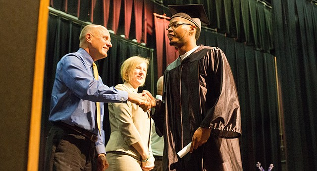 Dontra Mims, right, shakes hands with Lawrence schools superintendent Rick Doll as he receives his diploma during the Lawrence Adult Education Services graduation ceremony at Southwest Middle School, 2511 Inverness Drive, in this June 2015 file photo.