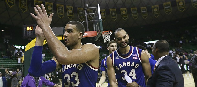 Kansas forward Landen Lucas (33) claps as he leaves the court to the applause of a handful of Jayhawk fans following their 66-60 win over Baylor, Tuesday, Feb. 23, 2016 at Ferrell Center in Waco, Texas. At right is Kansas forward Perry Ellis (34).
