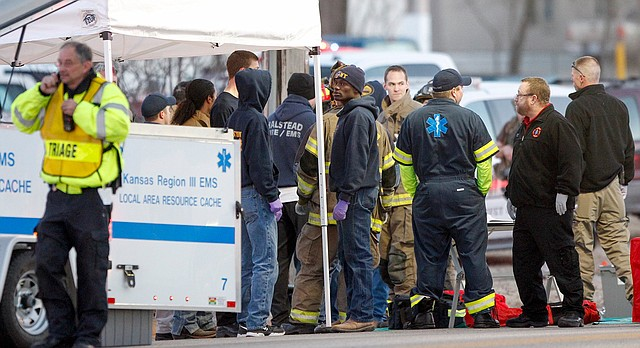 EMS workers gather a staging area by Excel Industries in Hesston, Thursday, Feb. 25, 2016, where a gunman killed an undetermined number of people and injured many more.