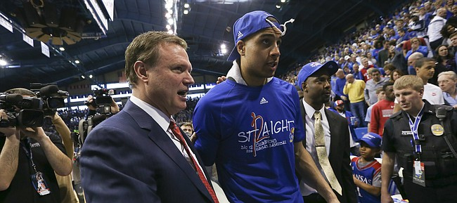 Kansas head coach Bill Self walks off with forward Landen Lucas after locking up a share of their twelfth-straight Big 12 title with the trophy following their 67-58 win over the Red Raiders, Saturday, Feb. 27, 2016 at Allen Fieldhouse.
