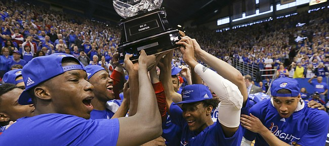 The Jayhawks celebrate locking up a share of their twelfth-straight Big 12 title with the trophy following their 67-58 win over the Red Raiders, Saturday, Feb. 27, 2016 at Allen Fieldhouse.