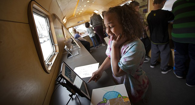 "New York School fourth-grader Richia Turner makes a silly face as she snaps her photo by way of an iPad and a digital photo booth program on Tuesday, March 1, 2016, outside the Lawrence Arts Center within the Kansas University MoCOLAB. The lab is an Airstream trailer used by LAC for arts education projects. Local elementary and middle school students toured the MoCOLAB, ""mobile colabratory,"" and spent some time working on digital art projects."