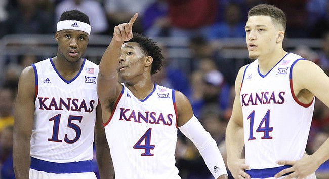 Kansas guard Devonte' Graham (4) gives some instruction to Kansas forward Carlton Bragg Jr. during the first half, Thursday, March 10, 2016 at Sprint Center in Kansas City, Mo. At right is Kansas guard Brannen Greene.
