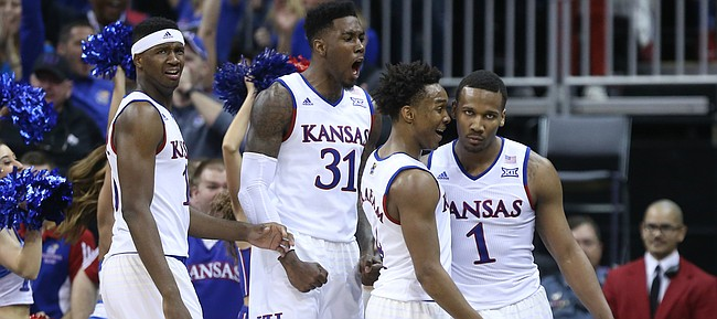 Kansas teammates Kansas forward Carlton Bragg Jr., left, Jamari Traylor, and Devonte Graham react to a thunderous dunk by guard Wayne Selden Jr. against Baylor during the second half, Friday, March 11, 2016 at Sprint Center in Kansas City, Mo.