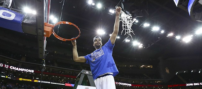 Kansas forward Perry Ellis hoists the net as the Jayhawks celebrate following their 81-71 win over West Virginia, Saturday, March 12, 2016 at Sprint Center in Kansas City, Mo.