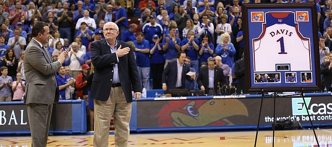 Broadcaster Bob Davis pats his heart as he receives a standing ovation from the fieldhouse before the final game of his 37-year career during a halftime ceremony on Saturday, March 5, 2016 at Allen Fieldhouse.