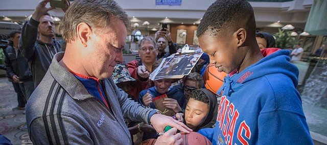 Kansas head coach Bill Self signs autographs for young Jayhawk fans upon the team's arrival at the Embassy Suites Downtown Des Moines, Iowa, Tuesday, March 15, 2016.