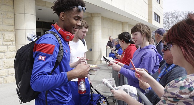 Kansas University guards Devonté Graham, front, and Tyler Self sign items for fans near the basketball facilities on KU's campus, Tuesday afternoon, March 22, 2016. The Jayhawks are heading to Louisville for the Sweet 16 of the NCAA Tournament, which begins Thursday.