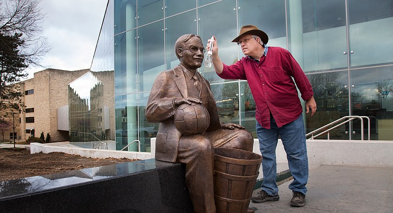 Bronze sculpture of James Naismith, inventor of basketball, takes a seat outside KU's DeBruce ...