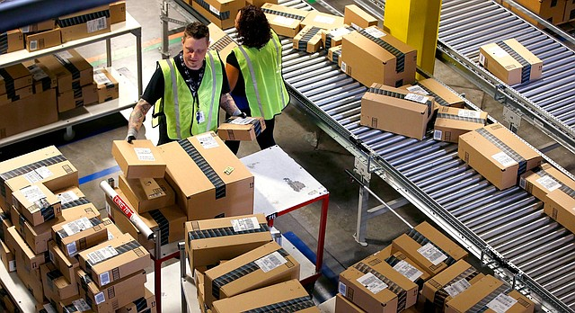 "In this Monday, Dec. 2, 2013, file photo, Amazon.com employees organize outbound packages at an Amazon.com Fulfillment Center on ""Cyber Monday"" the busiest online shopping day of the holiday season in Phoenix. (AP Photo/Ross D. Franklin, File)"
