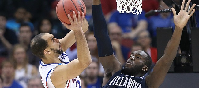 Kansas forward Perry Ellis (34) has a shot contested by Villanova forward Daniel Ochefu (23) during the second half, Saturday, March 26, 2016 at KFC Yum! Center in Louisville, Kentucky.