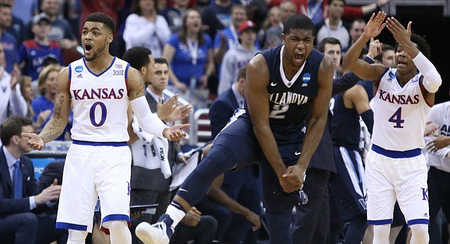 Kansas guards Frank Mason (0) and Devonte' Graham (4) look to the referees as Villanova's Kris Jenkins (2) celebrates during the first half of an NCAA Elite Eight matchup, Saturday, March 26, 2016, at KFC Yum! Center in Louisville, Kentucky.