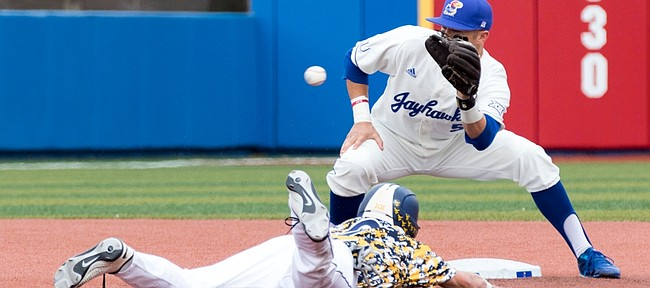 West Virginia freshman Kyle Gray slides in under the throw to Kansas sophomore Matt McLaughlin to steal second base during their game Saturday afternoon at Hoglund Ballpark.