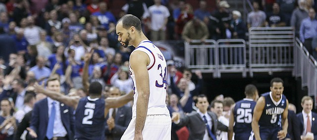 Kansas forward Perry Ellis (34) walks off the court as Villanova celebrates a 64-59 win over the Jayhawks Saturday, March 26, 2016 in an NCAA Elite Eight matchup at KFC YUM! Center in Louisville, KY. .