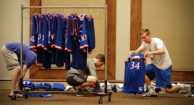 Kansas University men's basketball student managers, Chip Kueffer, Baldwin City, right, Jay Turnipseed, Houston, Texas, left, and Tim Skoch, Hastings, Neb., work to fold and bundle uniforms and other articles of clothing prior to a team meeting on Tuesday, Nov. 24, 2015 at the Westin Maui in Lahaina, Hawaii. The managers abide by a strict procedure for organizing and laundering all of the gear that accompanies the Jayhawks during their travels but often have to improvise on the road when faced with a quick turnaround between games.