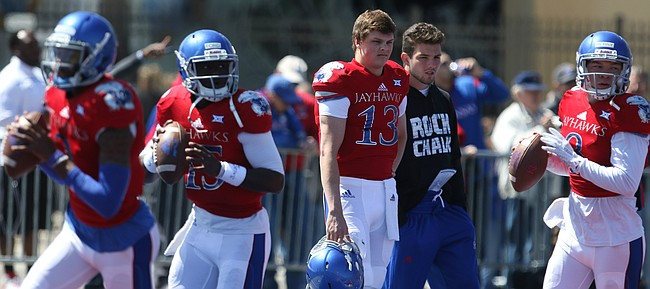 Injured Kansas quarterback Ryan Willis (13) watches from the sidelines as the rest of the quarterbacks warm up prior to kickoff of the Spring Game on Saturday, April 9, 2016 at Memorial Stadium.