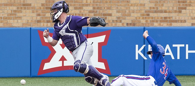 Kansas' Michael Tinsley slides into home plate while TCU catcher Evan Skoug chases down the ball during their game Sunday afternoon at Hoglund Ballpark.