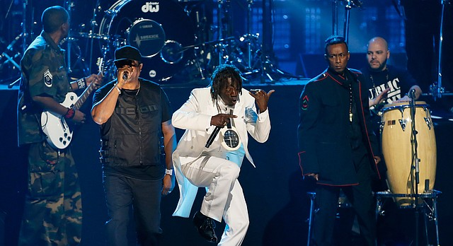 Chuck D, left, Flavor Flav, center, and Professor Griff, right, of Public Enemy perform during their induction at the Rock and Roll Hall of Fame Induction Ceremony at the Nokia Theatre on Thursday, April 18, 2013 in Los Angeles. (Photo by Danny Moloshok/Invision/AP)