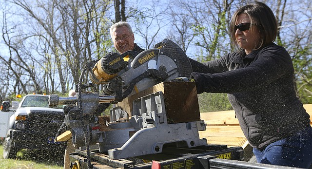 Volunteer Cris Bandle uses a miter saw to cut lengths of wood for an archery platform for campers on Saturday morning, April 9, 2016 at Lawrence Hidden Valley Camp, 3420 Bob Billings Parkway. In back is her husband, Jeff Bandle. Bandle says she has been involved with Hidden Valley Camp for about 15 years.