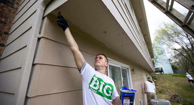 Naval ROTC midshipman Austin Pitcher, a Kansas University freshman from Clearwater, Kan., paints under an overhang at the home of Lawrence resident Geoff Coburn on Saturday as part of The Big Event, a day of volunteering organized by KU students. Volunteers went to parks, private residences and other locations across town to help with various beautification and cleanup projects.