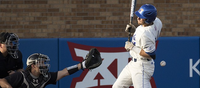 Kansas senior Colby Wright twists around as he is hit in the back with a pitch while Texas Tech catcher Tyler Floyd reaches for the ball during their game Friday evening at Hoglund Ballpark.