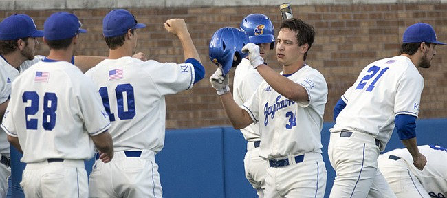 Kansas junior Michael Tinsley, center, is congratulated by teammates as he heads to the dugout after scoring during the Jayhawks' game against Texas Tech Friday evening at Hoglund Ballpark.
