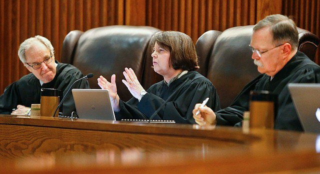 Kansas Supreme Court Justice Marla Luckert, center, asks a question to the state as they make their arguments in front of the Kansas Supreme Court, Tuesday May 10, 2016, in Topeka, Kan. The court was hearing arguments Tuesday on whether the technical changes approved by lawmakers earlier this year are fair enough to poor districts that the justices can abandon a threat to shut down public schools. (Chris Neal/The Topeka Capital-Journal via AP)