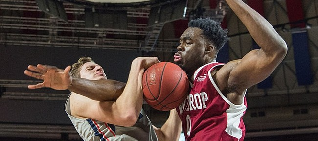 Liberty center Evan Maxwell, left, gets fouled hard by Winthrop's Duby Okeke in this photo from Feb. 2 in Lynchburg, Va. Maxwell, who is transferring to Kansas University, had 20 points in the game.