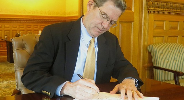 Kansas Gov. Sam Brownback signs a budget bill that makes significant cuts to the highway fund, Medicaid and higher education, Wednesday, May 18, 2016.