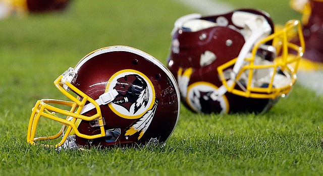 FILE - In this Dec. 26, 2015, file photo, a Washington Redskins helmet sits on the field as players warm-up before an NFL football game against the Philadelphia Eagles in Philadelphia. (AP Photo/Matt Rourke, File)