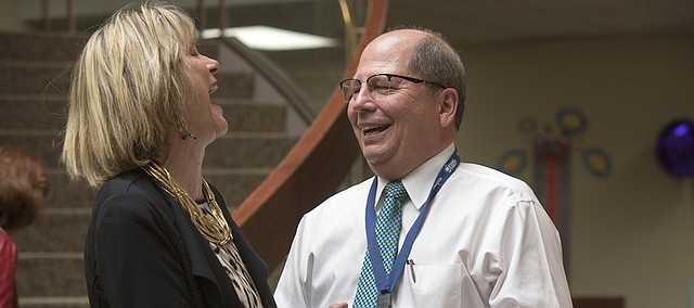 Sharon Spratt, CEO of Cottonwood Inc., left, and Gene Meyer, outgoing president and CEO of Lawrence Memorial Hospital, share a humorous moment Wednesday afternoon during Meyer's retirement reception at LMH.